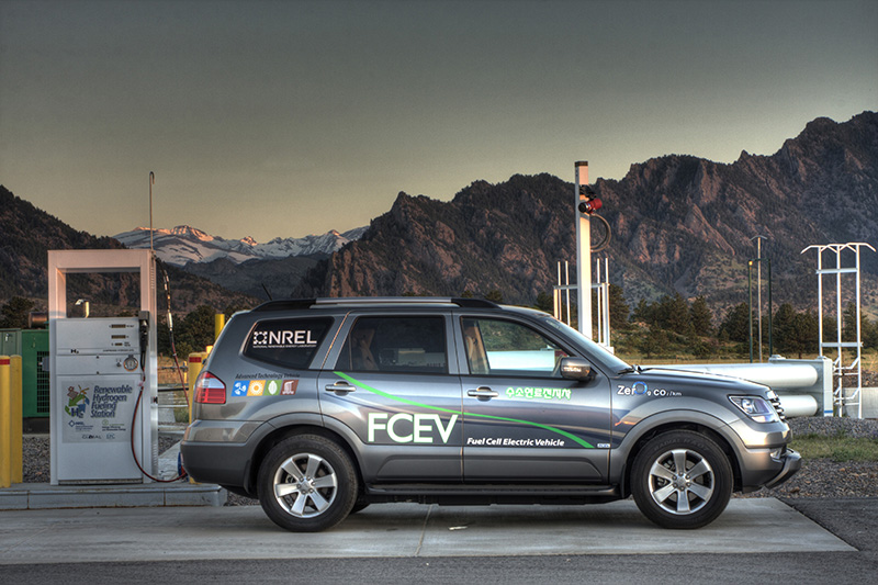 SUV vehicle in front of a fueling station with mountains in the backgroud